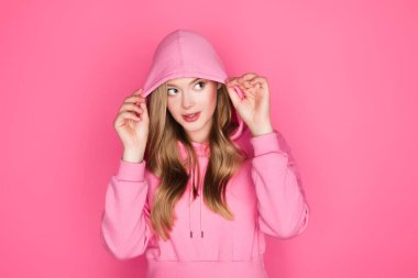 Beautiful young woman in hoodie on pink background stock vector