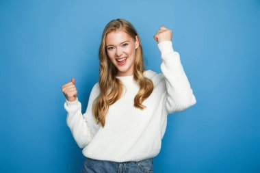 Happy blonde beautiful woman in sweater showing yeah gesture isolated on blue background stock vector