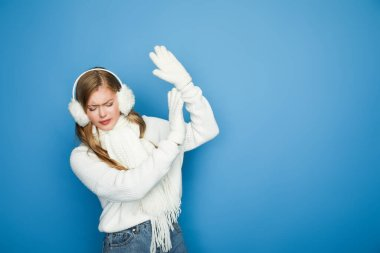 beautiful woman in winter white outfit showing stop gesture isolated on blue