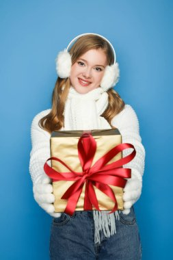 Smiling beautiful woman in winter white outfit giving gift box isolated on blue stock vector