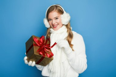 Smiling beautiful woman in winter white outfit with gift box isolated on blue stock vector