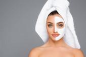 Frau mit Handtuch auf dem Kopf und Tonmaske auf dem Gesicht isoliert auf grau