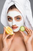 Frau mit Handtuch auf dem Kopf und Tonmaske im Gesicht, die Zitrone und Gurke isoliert auf grau hält