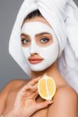 Frau mit Handtuch auf dem Kopf und Tonmaske im Gesicht, die Zitrone isoliert auf grau hält