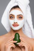 Frau mit Handtuch auf dem Kopf und Tonmaske im Gesicht, die Avocadohälften isoliert auf grau hält
