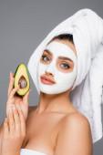 Frau mit Handtuch auf dem Kopf und Tonmaske auf dem Gesicht, die Avocado isoliert auf grau hält