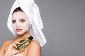Frau mit Handtuch auf dem Kopf und Maskentuch im Gesicht, Flasche isoliert auf grau