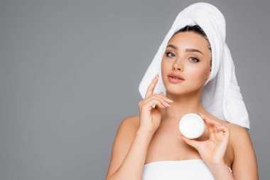 Woman with towel on head applying cosmetic cream on face isolated on grey stock vector