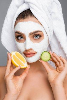 Kafasında havlu ve yüzünde kil maske olan bir kadın gri renkte limon ve salatalık tutuyor.