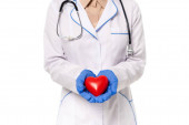 Cropped view of doctor holding red heart isolated on white