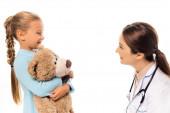 Lächelnder Kinderarzt sieht Mädchen mit Stofftier isoliert auf weißem Grund an