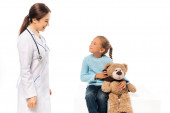 Doctor smiling at girl with teddy bear on table isolated on white
