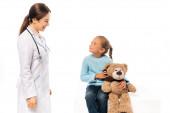 Arzt lächelt Mädchen mit Teddybär auf weißem Tisch an