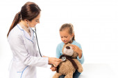 Smiling doctor examining with stethoscope soft toy near girl isolated on white