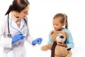 Arzt in Latex-Handschuhen hält Baumwolle und Spritze in der Nähe von Mädchen mit Teddy-Beat isoliert auf weiß