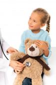 Fotografie Lächelndes Kind hält Kuscheltier in der Nähe von Arzt mit Stethoskop isoliert auf weiß