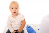 Selektiver Fokus des Kleinkindes, das mit weißer Spritze in die Kamera in der Nähe des Arztes blickt