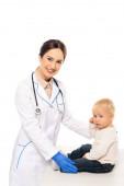 Lächelnder Kinderarzt blickt in Kamera neben Kleinkind auf weißem Tisch
