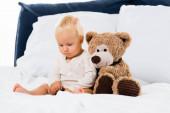 Selektivní zaměření batole sedí v blízkosti měkké hračky na posteli na bílém pozadí