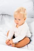 Selektivní zaměření blondýny batole chlapec sedí na bílém lůžku