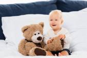 Selektivní zaměření batole chlapec usmívá poblíž medvídek na posteli na bílém pozadí
