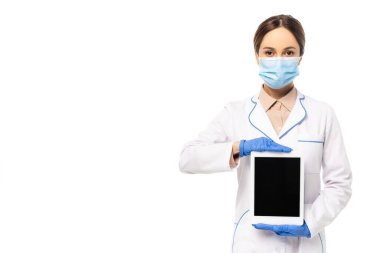Doctor in latex gloves and medical mask showing digital tablet with blank screen isolated on white stock vector