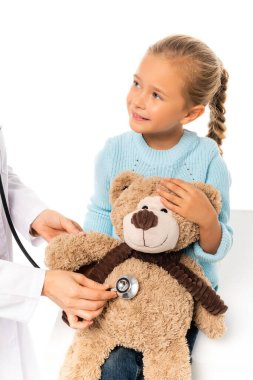 Smiling child holding soft toy near doctor with stethoscope isolated on white stock vector