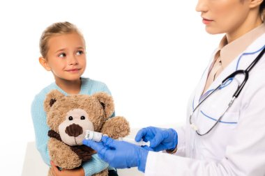 Selective focus of smiling girl with teddy bear sitting near doctor with syringe and vaccine isolated on white stock vector