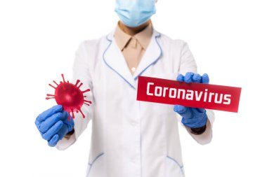 Cropped view of doctor holding card with coronavirus lettering and bacteria isolated on white stock vector