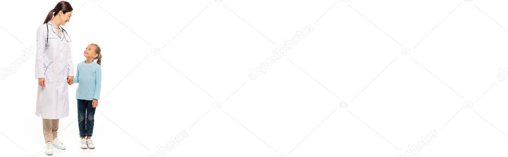 Panoramic crop of pediatrist smiling and holding hand of girl on white background stock vector