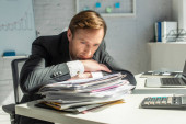 Disappointed businessman leaning on pile of papers, while sitting at workplace on blurred background