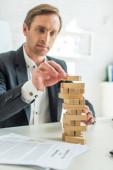 Zaměřený podnikatel stavební bloky dřeva hry, zatímco sedí na pracovišti s rozmazané petice za bankrot v popředí