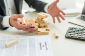 Cropped view of businessman with hands near block wood game falling near petition for bankruptcy on blurred background