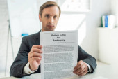 Serious businessman looking at camera and showing petition for bankruptcy, while sitting at desk on blurred background