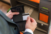 Cropped view of businessman putting credit card in wallet, while standing near atm on blurred foreground