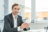Positive businessman with smartphone looking at camera, while siting at workplace with blurred window on background