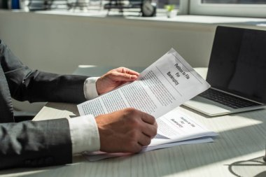 Cropped view of businessman holding petition for bankruptcy, while sitting at workplace on blurred background stock vector