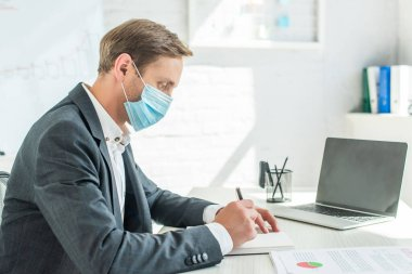 Side view of businessman in medical mask, writing in blank notebook, while sitting at workplace on blurred background stock vector