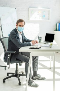 Full length of businessman in medical mask looking at camera, while writing in notebook, sitting at workplace in office stock vector