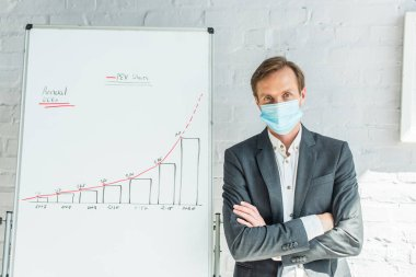 Businessman wearing medical mask and looking at camera, while standing near flipchart with graph stock vector