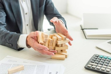 Cropped view of businessman holding blocks wood game collapsing, while sitting near documents at workplace