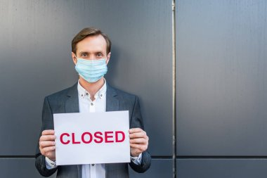 Front view of businessman in medical mask, holding sign with closed lettering on grey textured background stock vector