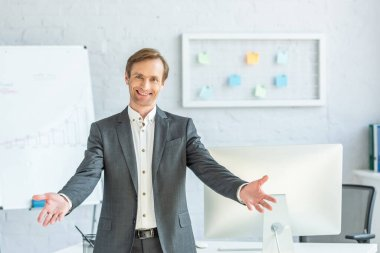 Front view of happy businessman with open arms looking at camera with blurred office on background stock vector