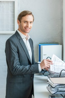 Happy businessman looking at camera, while searching paper in document tray on windowsill stock vector