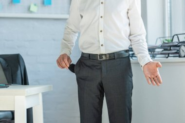 Cropped view of businessman gesturing and showing empty pocket, while standing near workplace on blurred background stock vector