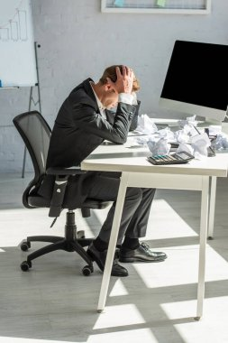 Full length of depressed businessman with hands on head, sitting at workplace with crumbled papers stock vector