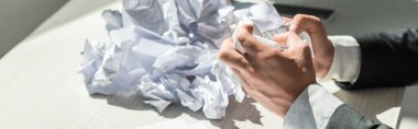 Cropped view of businessman with hands near pile of crumbled papers on blurred background, banner stock vector