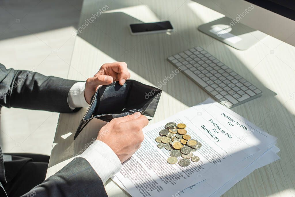 Cropped view of businessman holding empty wallet near coins and petitions for bankruptcy on workplace stock vector
