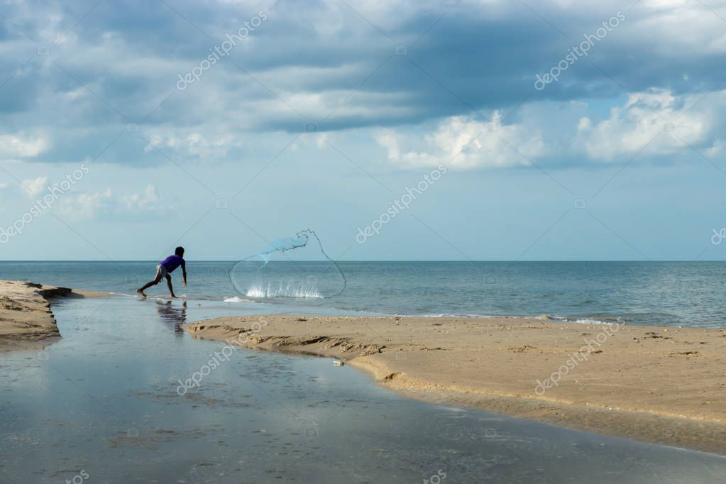 minimal of fisherman are casting net on the beach.