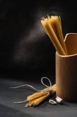 raw spaghetti with garlic on black surface